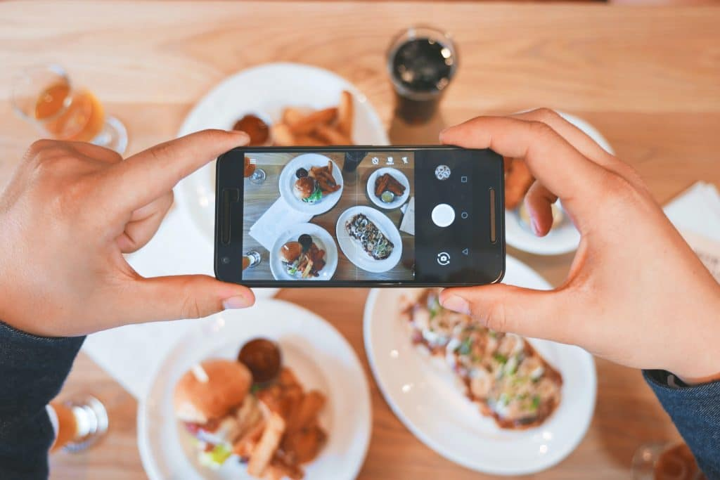 Pair of hands taking a photo of beautiful plates of food on a wooden table for user-generated content.